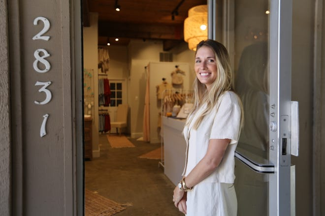 Madison Schmidtlein, owner of Madison Avenue Boutique, stands at the entrance of her new shop. The boutique opened Saturday in Brookwood Shopping Center, at 2831 S.W. 29th St.