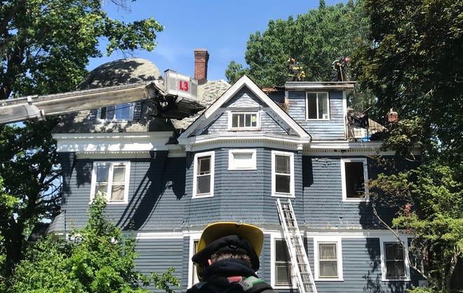 Firefighters check for hot spots at a three-alarm fire at 40 May St. on Saturday in Worcester.