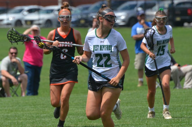 West Deptford junior Krista Yarusso runs through the midfield with Middle Township Jade Nagle and freshman Kassidy Yarusso, her sister, trailing the play