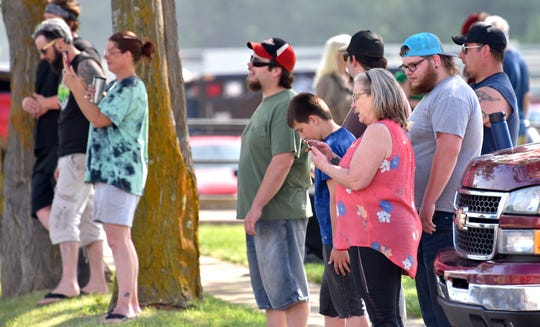 People watch firefighters fight the blaze in downtown Lapeer on Saturday, June 5, 2021.