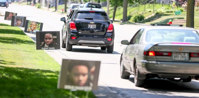 Signs that had photographs of people who have been fatally shot in Milwaukee line the street for a memorial drive-by event organized by Wisconsin Chapter of Mothers Demand Action for Gun Sense on Saturday, June 5, 2021, near Center Street and Sherman Boulevard. There were 18 photographs of people who have died from gun violence along the memorial.
