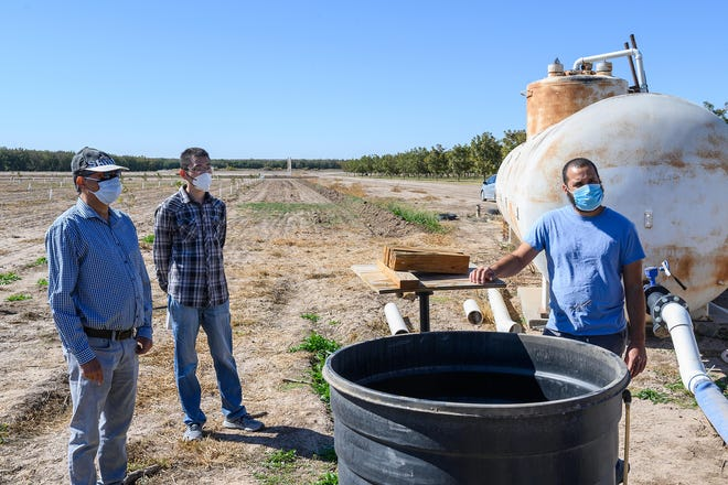 New Mexico State University College of Agricultural, Consumer and Environmental Sciences professor Manoj Shukla, left, Chang Liu, center and Adam Gonzalez, right, explain the N-Drip's Gravity Micro Irrigation system at NMSU's Leyendecker Plant Science Research Center.