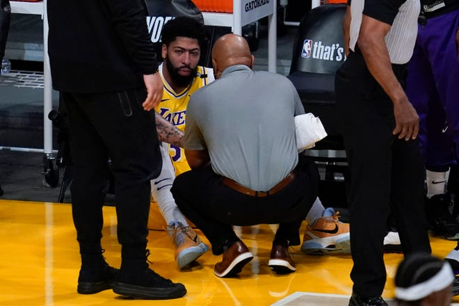 Los Angeles Lakers forward Anthony Davis (3) is checked out for injury during the first quarter of Game 6 of an NBA basketball first-round playoff series Thursday, Jun 3, 2021, in Los Angeles. Davis let the court. (AP Photo/Ashley Landis)