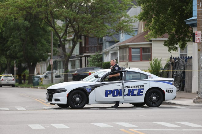 A Rochester police officer blocks at intersection at Avenue D and Hudson Avenue after a man was shot and killed by RPD June 4.