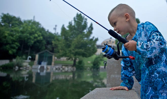 Linton Herrick checks the waters of the Concho River off the Celebration Bridge for fish during the annual youth fishing derby Saturday, June 5, 2021.