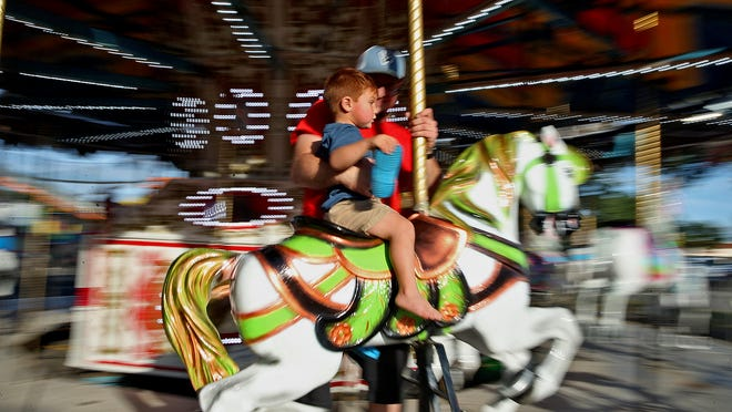 Elijah Loos, center, rides the carousel with his father Quinton Loos at a carnival at the Sunset Mall on Thursday, June 3, 2021.