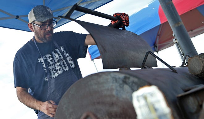Ernie Acevedo checks on food cooking on a grill at Lake Nasworthy during the Beers, Bands and BBQ Festival on Friday, June 4, 2021.