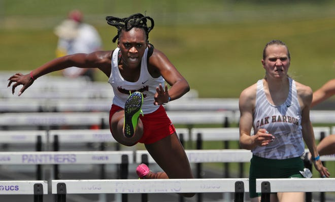 Buchtel's DaMya Barker, left, clears a hurdle ahead of Oak Harbor's Amelia Mizelle in the girls 100-meter hurdles event during the Division II state track & field meet at Pickerington High School North on Saturday. [Jeff Lange/Beacon Journal]