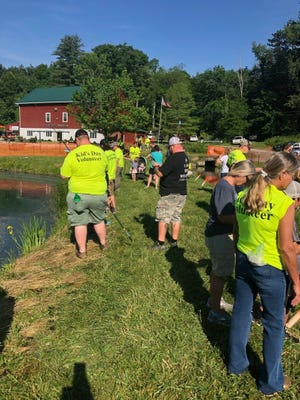 Volunteers help kids fish during Saturday's Kids Outdoor Day at the Ashland County Wildlife Conservation League farm.