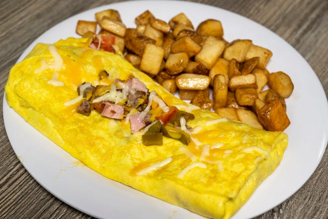 The Grillman's omelet features bacon, sausage, ham, onions, peppers, tomatoes and cheese served with home fries for $9.29.