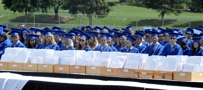 Wooster High School's graduating seniors listen Sunday to speeches before they receive their diplomas at the WHS graduation ceremony. Over 250 students graduated, earning  more than $6 million n scholarships.