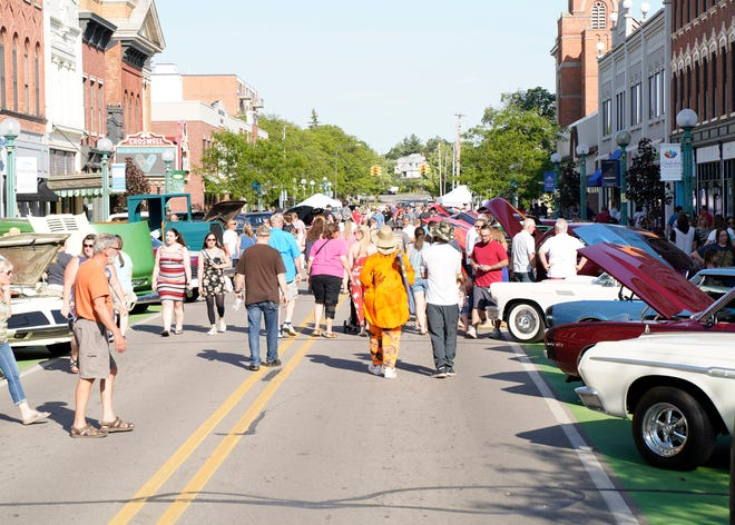 People stroll down Maumee Street among the classic cars in downtown Adrian June 4 during First Fridays.