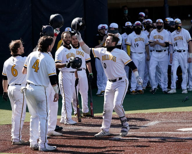 Adrian College's Gunner Rainey is greeted at home by Thomas Miller (4) and Ty Peck (6) after hitting a home run in the 2021 season.