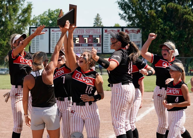 The Clinton softball team and head coach Kim Phillip celebrate with the trophy after winning their Division 3 district championship over Madison, 7-2, on Saturday.