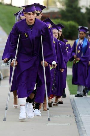 Los graduados de Burlington High School, incluido Blake Myers en muletas, se dirigen a recoger sus diplomas durante el ejercicio de graduación de la escuela, el sábado 5 de junio de 2021, en el estadio Bracewell.  Myers recibió un disparo la noche anterior en las piernas mientras asistía a una fiesta.