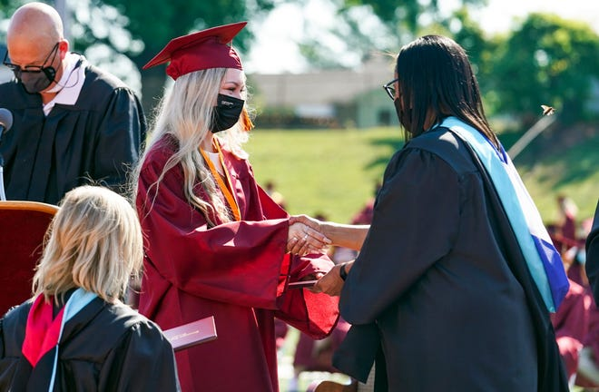 Graduate Lily Ray receives her diploma Saturday morning from Bloomington High School North principal Michelle Brittain-Watts during the graduation ceremony.