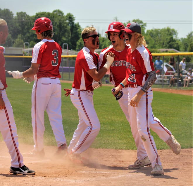 Bedford's Ethan Brickner celebrates at home plate with his teammates after hitting a home run against Monroe in the Division 1 District semifinals. Brickner was one of four Bedford Bedford players to make the All-SEC Red team. Two Monroe players made it as well.