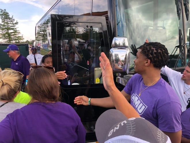 Spurs forward Keldon Johnson greets cousin Odicci Alexander as she boards the James Madison bus.