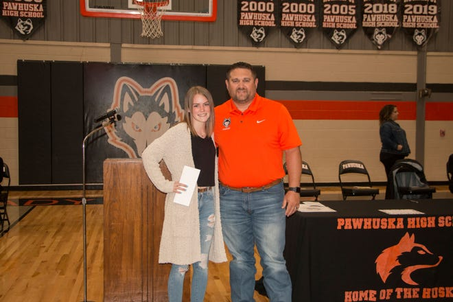 Kellie Trammel receives a $3,000 scholarship from Danny Ferguson of American Heritage Bank in Pawhuska. Trammel received the scholarship award during an end-of-school-year assembly at Pawhuska High School.