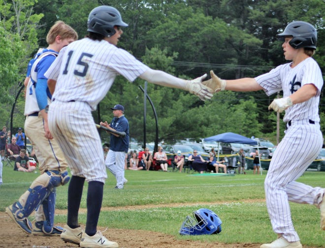 St. Thomas' Adam Stewart (15) congratulates Tim Avery (1) after Avery plated Stewart with a sacrifice fly in the top of the seventh inning to give St. Thomas a 3-1 lead over Oyster River in Saturday's Division II quarterfinal.