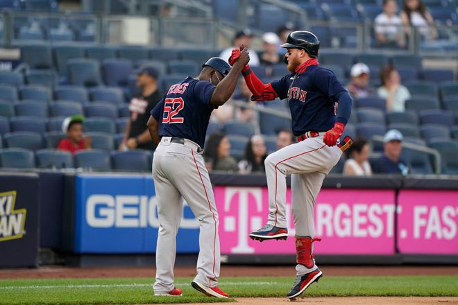 Red Sox outfielder Alex Verdugo, right, celebrates with third-base coach Carlos Febles after hitting a solo home run in the first inning of Sunday night's game against the Yankees in the Bronx.
