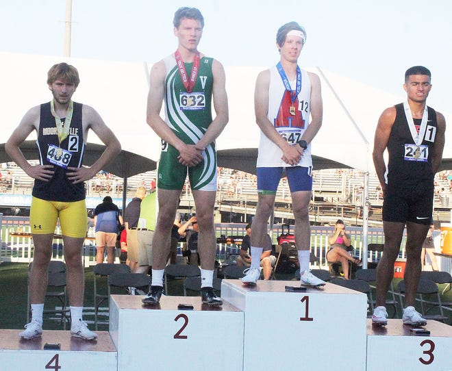 Mooresville senior Mason Wolfe (left) takes his place on the 800-meter podium Friday, joining winner William Newbauer of South Bend Adams, runnerup Brett Otterbacher of Valparaiso and third-place finisher Jaylen Castillo of Fishers. (Steve Page / Correspondent)