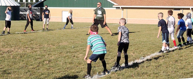 Monrovia head football coach Andy Olson directs campers at the start of jumping jacks during the opening session of the Monrovia Bulldogs Youth Football Camp in 2020. (Steve Page / Correspondent)