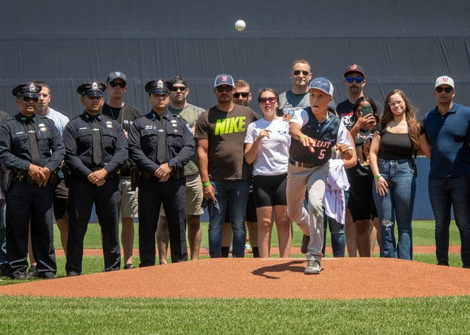 Jovan Familia, the 13-year-old son of Worcester Police Officer Enmanuel Familia, throws out the ceremonial first pitch surrounded by family and officers at Polar Park on June 6, 2021.