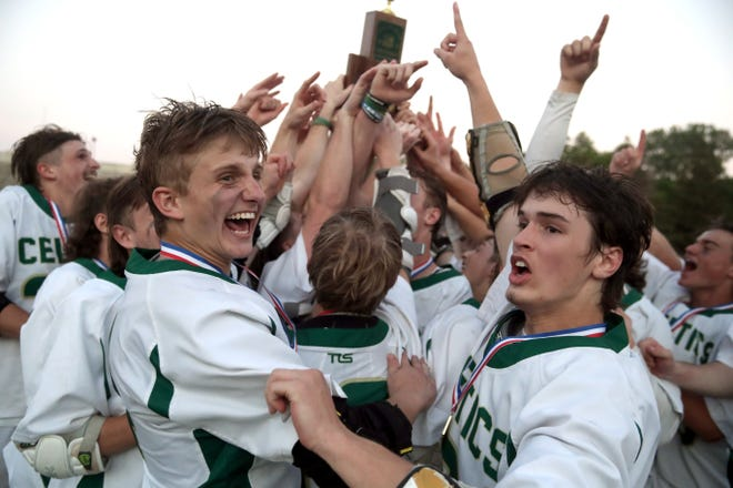 Dublin Jerome's Marek Tzagournis, left, and Luke McLoughlin, right, celebrate with teammates after a 12-11 victory over Upper Arlington in the Division I state final June 5 at Ohio Wesleyan.