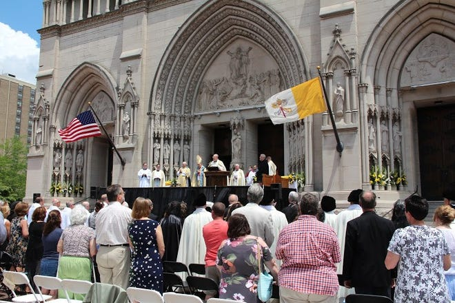Rev. Ryan Maher, vicar general for the Diocese of Covington and rector of the Cathedral Basilica of the Assumption, speaks at the podium during the dedication of the cathedral's new façade on June 6, 2021.