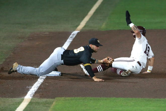 Mississippi State's Logan Tanner slides safely into third against Virginia Commonwealth's Tyler Locklear during the first inning of an NCAA college baseball tournament regional game Saturday, June 5, 2021, in Starkville, Miss. (Adam Robison/The Northeast Mississippi Daily Journal via AP)