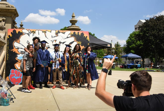 Andrew Constans takes a picture of Eastern High School graduates with Erica and Michael Lynn, left, founders of The Village Lansing, Sunday, June 6, 2021, during the second-annual graduation celebration they helped organize at the state Capitol.
