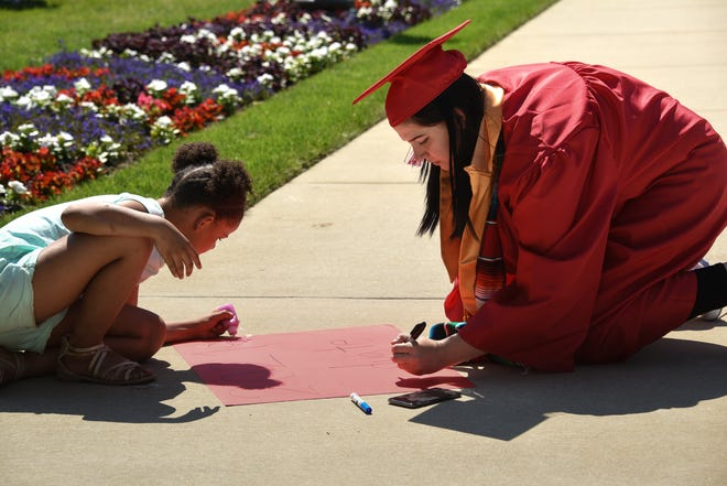 """""""I want to work for NASA,"""" Sexton grad Meghann Cervantes says, shown here making a poster with niece Justine Long, 8, Sunday, June 6, 2021, during the second-annual graduation celebration at the Capitol organized by The Village Lansing. The salutatorian will attend Arizona State University in the fall and plans to study astrobiology."""
