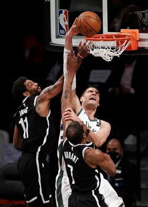 Bucks center Brook Lopez dunks between Nets forward Kevin Durant and guard Kyrie Irving.
