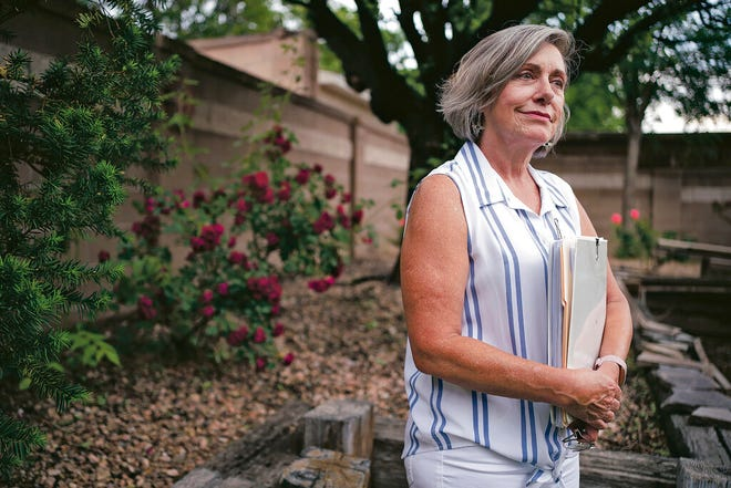 Gladys Waltman holds a binder of news clippings, autopsy reports and various documents related to her niece Teal Pittington's cold case in her backyard in Albuquerque on Wednesday, May 26, 2021. The Santa Fe beauty school student Pittington disappeared in the summer of 1984.