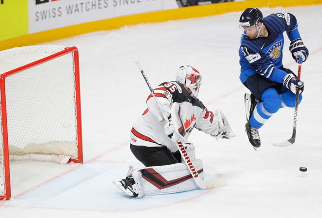 Finland's Iiro Pakarinen, right, and Canada's goaltender Darcy Kuemper in action during the Ice Hockey World Championship final match between Finland and Canada at the Arena in Riga, Latvia, Sunday, June 6, 2021. (AP Photo/Sergei Grits)