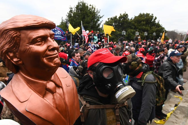 Protester in gas mask holds bust of Donald Trump after storming the U.S. Capitol on Jan. 6, 2021.