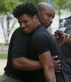 Marcus Wattley, former McKinley High School head football coach, gets a hug from one of his players Monday following a disciplinary hearing at the Canton City School District's administrative office. District leaders are determining whether Wattley can keep his noncoaching job with the district.