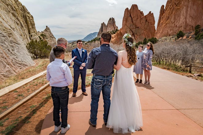 Kim Combes of Colo officiates the wedding of Matt, his adoptive son, and Whitney, the daughter of his former foster client.