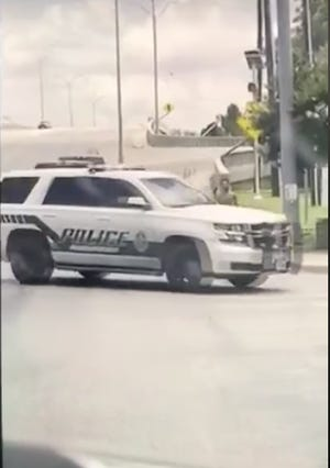 In a video screen grab, a Brownwood police car turns across the path of a man who was running naked along the Austin Avenue overpass Sunday afternoon.