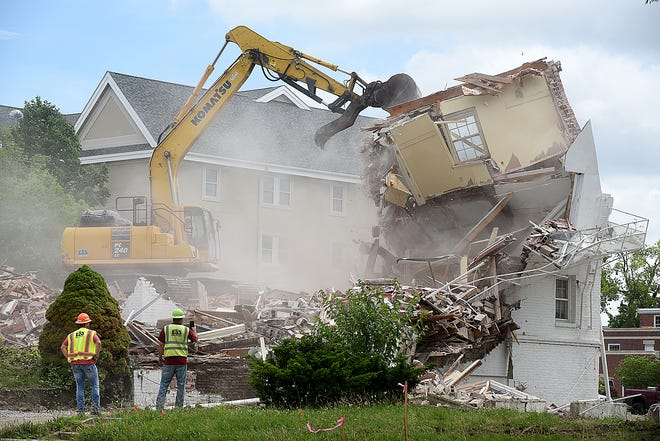 Emery Sapp & Sons workers watch as a trackhoe operator brings down the last part of the Alpha Phi sorority building Monday. About two dozen present and former Alpha Phi members watched from across the street. A new Alpha Phi house will be built in the same location.