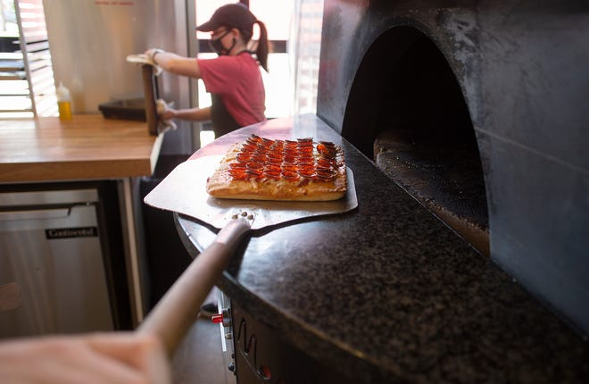 Emily Gatton preps pizza pans as a fresh cooked pizza comes out of the oven at Wizard of Za in Clintonville.