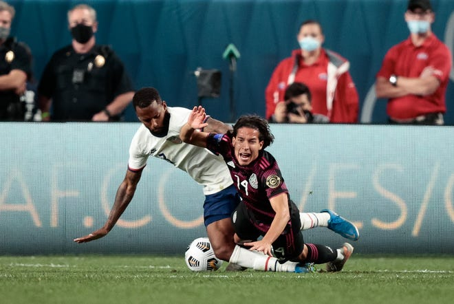 U.S. midfielder Kellyn Acosta and Mexico midfielder Diego Lainez battle for the ball in the second half during the CONCACAF Nations League final on Sunday.