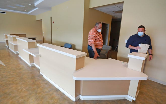 Jason VanPeteghen, facilities maintenance manager of I Am Boundless, left, and Andy Hardy, OhioHealth's external affairs manager, look over an expansive front desk at OhioHealth's Westerville Medical Campus. I AM Boundless is one of three nonprofit groups receiving furnishings, building materials and other items being salvaged from a renovation of the Westerville campus.