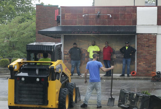Crew members from Tri-County Asphalt wait under an awning as others on their team work to improve the parking lot of Cafe Istanbul on Main Street in Bexley as rain showers roll through the Columbus area on Monday morning.