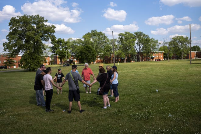 The Rev. Johnny Amos of Shiloh Christian Center leads a prayer walk Saturday in the area around Wedgewood Village Apartments, part of a series of prayer walks scheduled around the area this summer.