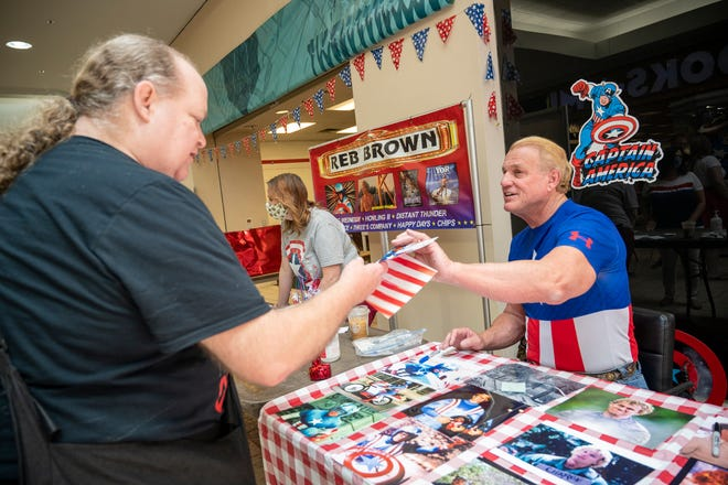 Reb Brown signs a photo for a fan at Comic-Fest at Lake Square Mall on Sunday. [Cindy Peterson/Correspondent]