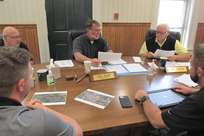 Holmes County Commissioners Ray Eyler, Rob Ault and Joe Miller discuss a proposal for new wireless internet system for county buildings with co-owners Kyle Yoder (front left) and Dean Anderson of Blueshift Wireless.