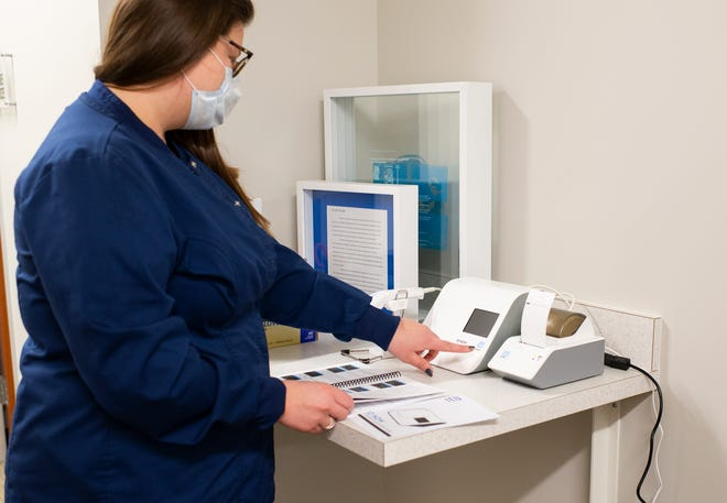 Margaret Sims, a medical assistant in Adrian College's Student Health Center, is pictured with the college's new Abbott ID Now testing machine, which is similar to a Polymerase Chain Reaction (PCR) test and is highly accurate, the college said. The testing machine can detect Strep A, Flu A and B, RSV and COVID-19, through direct nasal, nasopharyngeal or throat swabs.