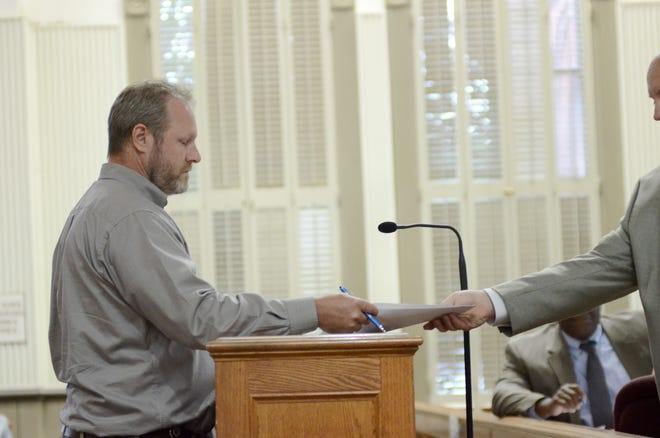 Ascension Parish President Clint Cointment receives a lawsuit from District 4's Corey Orgeron during the July 3 Ascension Parish Council meeting at the courthouse in Donaldsonville.